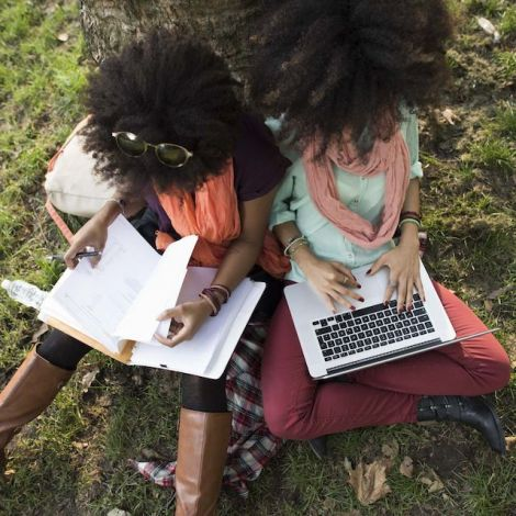 Zwei Studentinnen im Auslandsstudium unter einem Baum