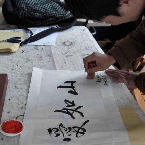 Lukas zeichnet chinesische Schriftzeichen