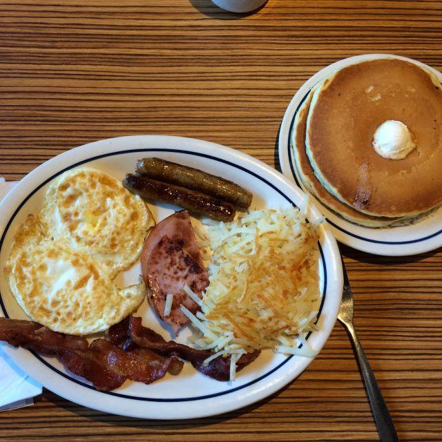 Eier, Bacon, Würstchen, Kartoffeln und Pancakes mit Butter & Syrup