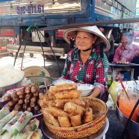 Frau verkauft Rollen und andere Speisen
