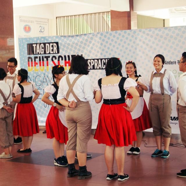 Vietnamesen tanzen deutsche Tänze in Lederhose und Dirndl