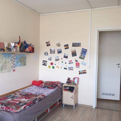 Bett in einem Zimmer, an der Wand Fotos und Landkarten