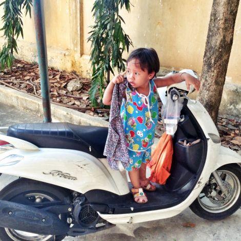 Kind auf stehendem Motorroller