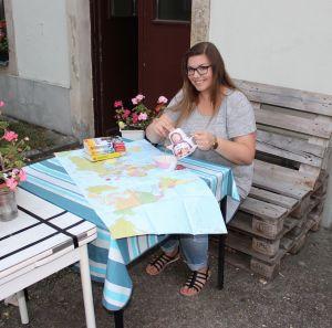 Vanessa mit Weltkarte und Reiseführern vor dem Haus
