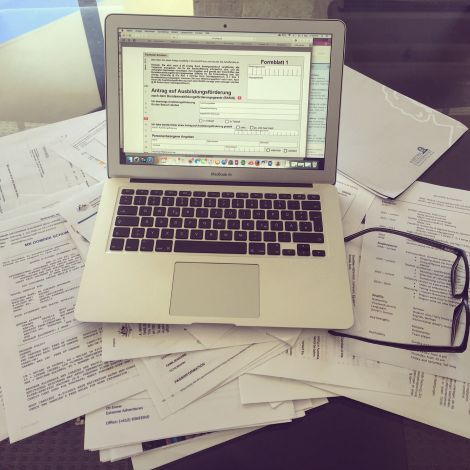 Laptop und haufenweise Formulare