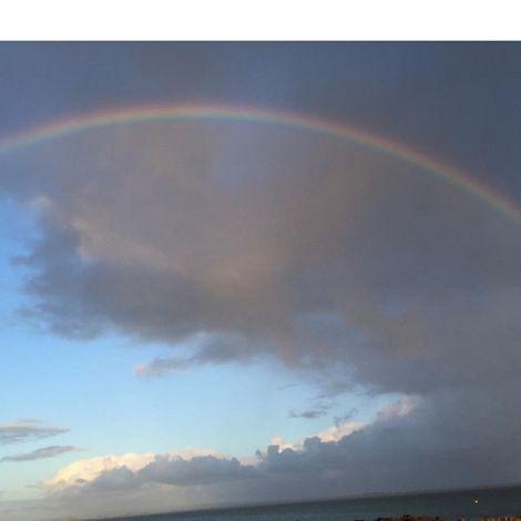 Regenbogen vor Wolken und blauem Himmel