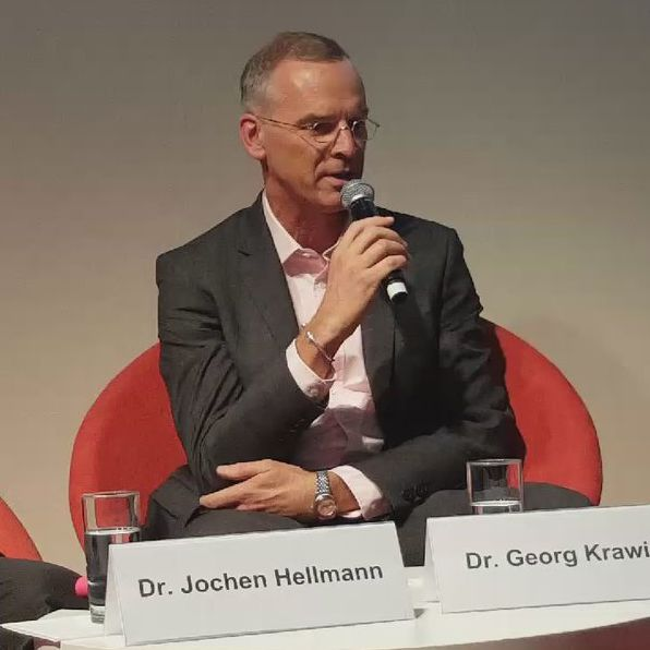 Dr. Georg Krawietz während der Podiums-Diskussion mit einem Mikrophon in der Hand