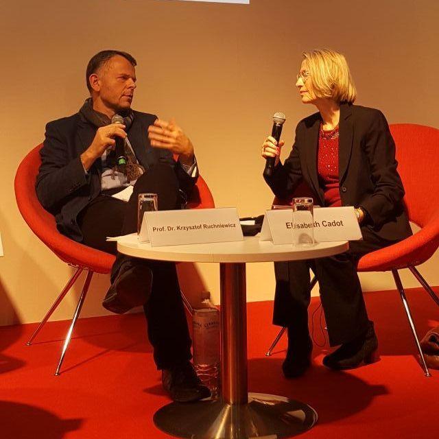 Prof. Dr. Ruchniewicz an einem Tisch und im Gespräch mit Mme Cadot