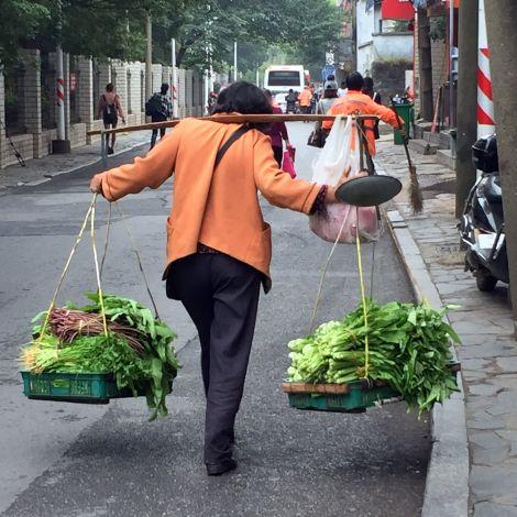 Mensch in China trägt Gemüse auf der Straße