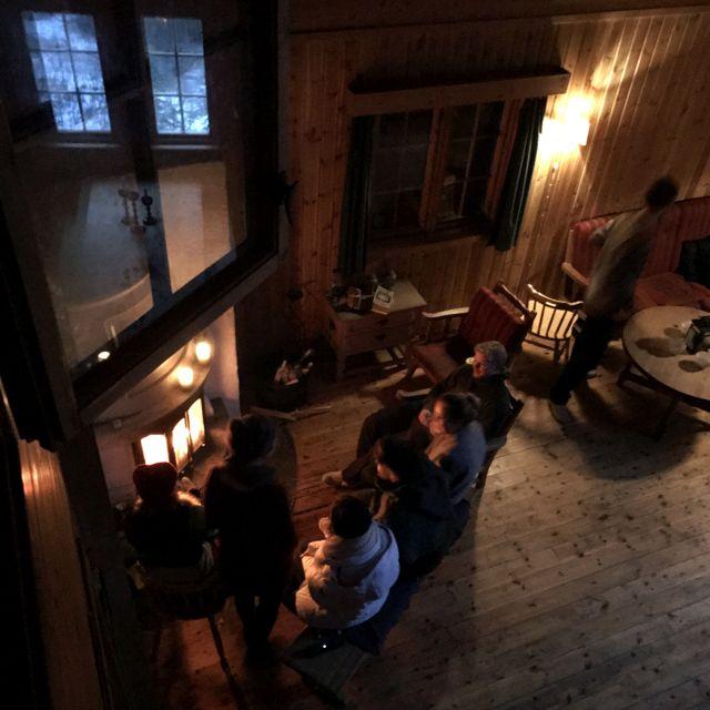 Mehrere Menschen sitzen in der Waldhütte Grønlihytta vor einem brennenden Kamin