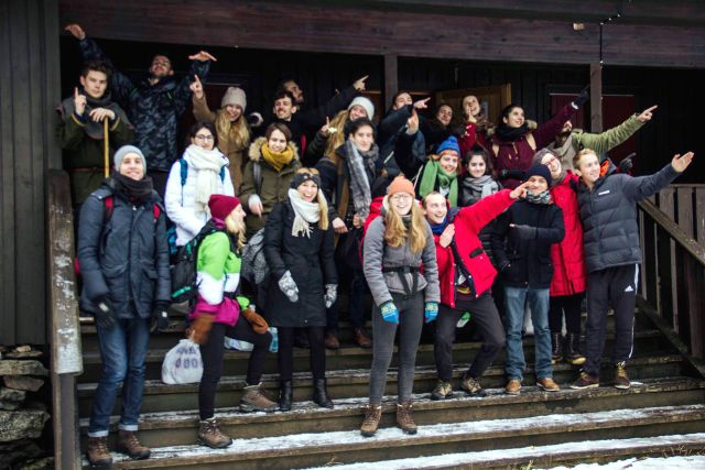 Die Gruppe von Austauschstudenten steht vor der Grønlihytta und verabschiedet sich mit verschiedenen Gesten
