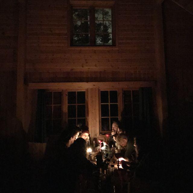 Studenten sitzen bei Kerzenschein an langen Holztischen in der Hütte