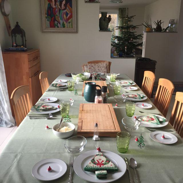 Weihnachtlich gedeckter Tisch, im Hintergrund ein Weihnachtsbaum