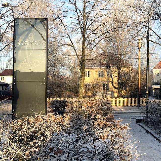 Schild der Uni Oslo vor einem Holzhaus