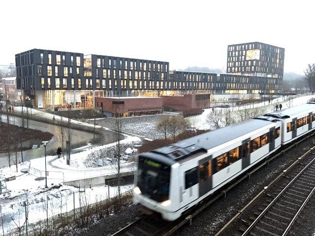 Fahrende U-Bahn vor Universitätsgebäude