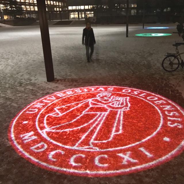 Wappen der Uni Oslo auf den verschneiten Boden projiziert