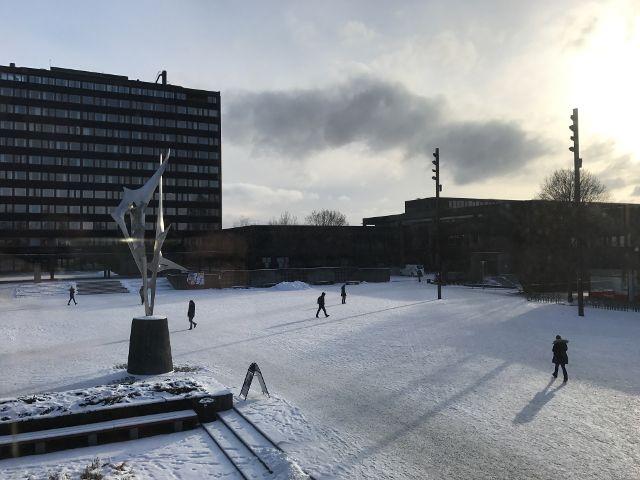 Skulptur auf dem verschneiten Campusgelände, Hochhaus im Hintergrund