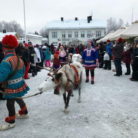 Traditionell gekleidete Sámi mit Rentieren durch die Stadt ziehend