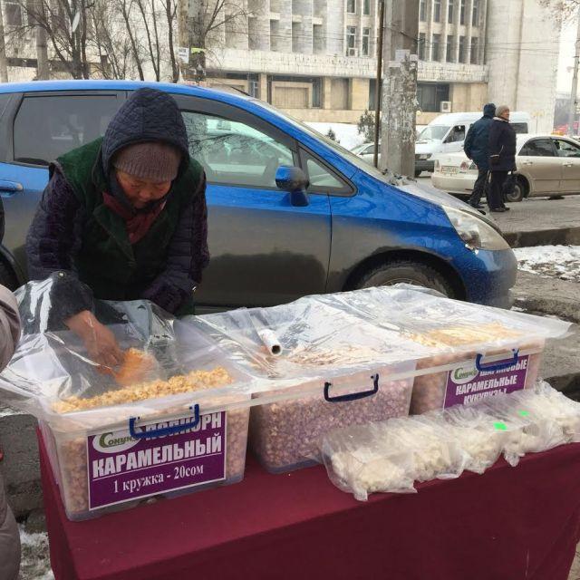 Frau verkauft Popcorn in der Stadt auf der Straße