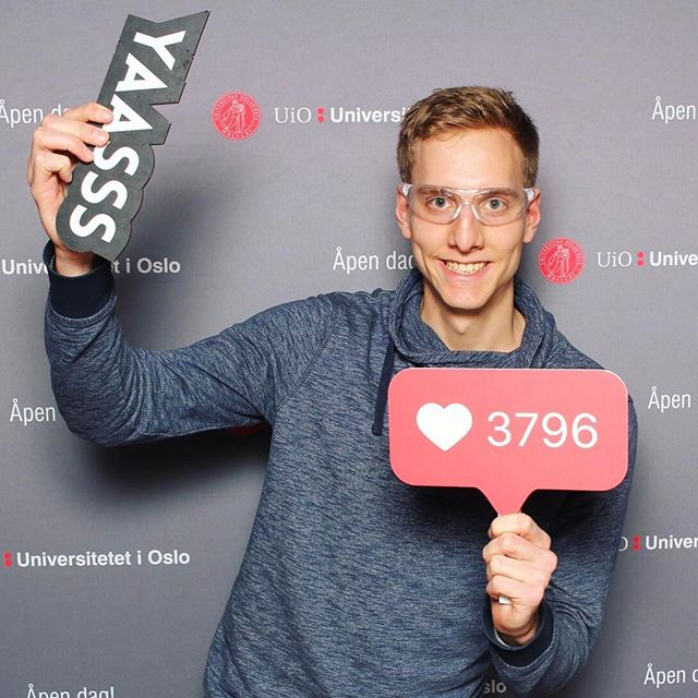 Mann mit Laborbrille vor Stellwand der Uni Oslo