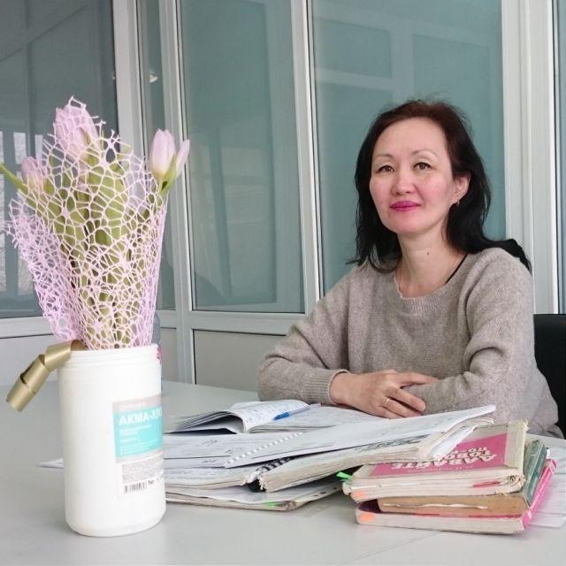Kasachische Lehrerin an ihrem Schreibtisch mit einem Strauß Blumen und Russischbüchern vor sich.