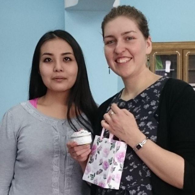 Theresa mit einer ihrer Studentinnen neben sich und einem Geschenk in der Hand.