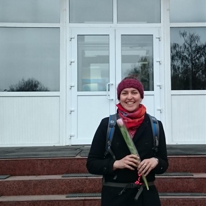 Theresa mit einer Tulpe in der Hand vor dem Gebäude der Almatiner Technischen Universität.