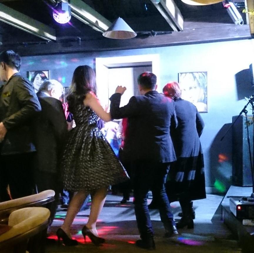 Tanzende Leute in einem Cafe in Almaty zum Frauentag