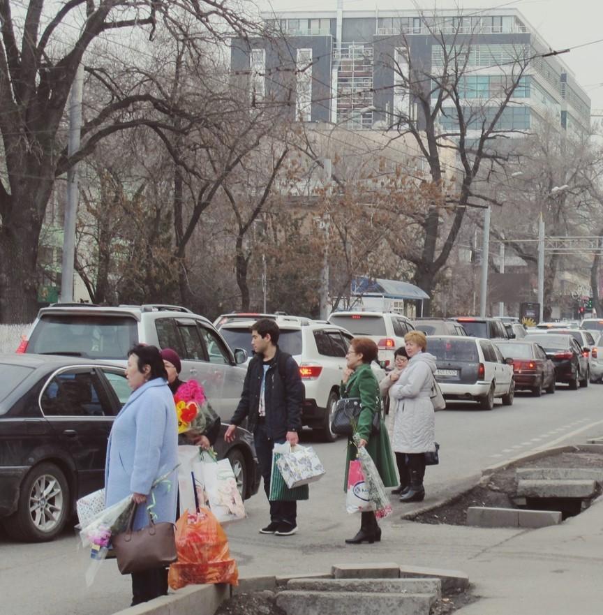 Auf Bus oder Taxi wartende Frauen mit Einkäufen und Blumen in der Hand.