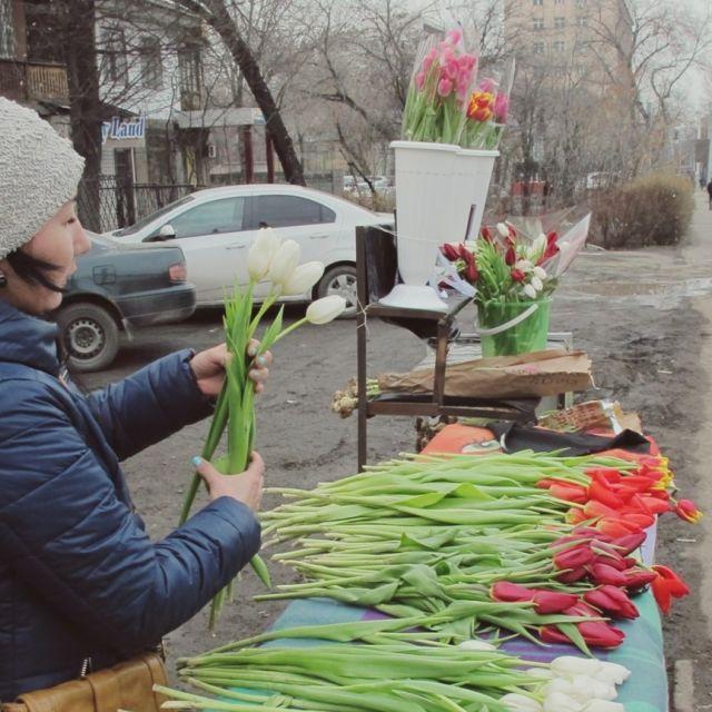 Verkäuferin die einen Tulpenstrauß zusammenstellt am Straßenrand in Almaty