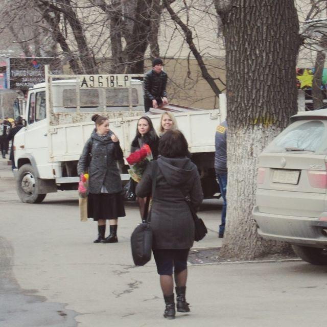 Frauen auf dem Gehweg mit Blumen in der Hand.
