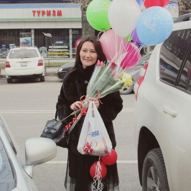 Junge, freundlich lächelnde Frau mit Luftbalons, Blumen und Tüten bepackt.