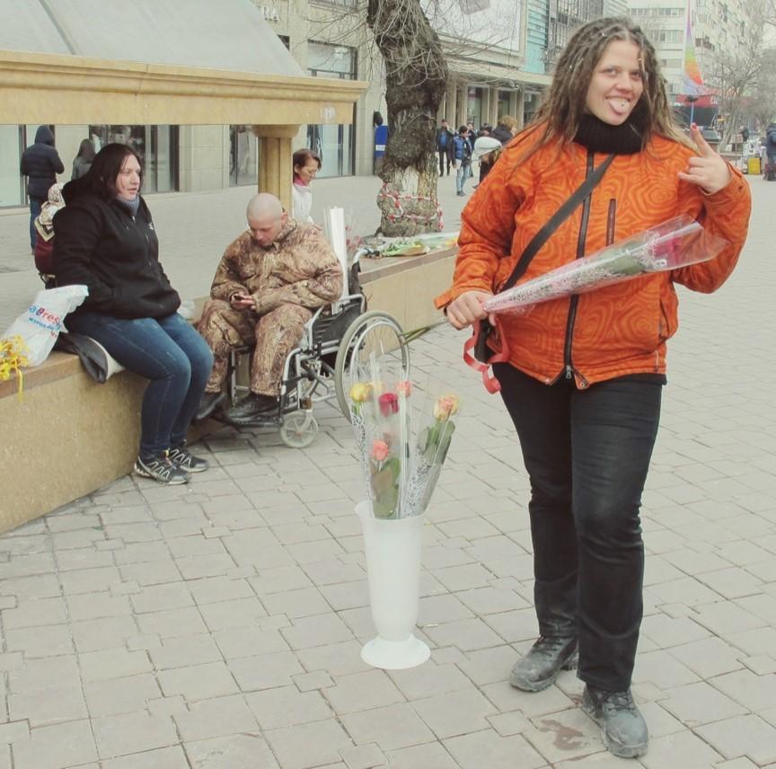 Rosenverkäuferin in der Almatiner Fußgängerzone posiert mit einer Rose in der Hand.
