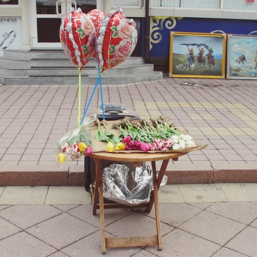 Tisch in der Fußgängerzone auf dem Tulpen und herzförmige Heliumluftbalons angeboten werden