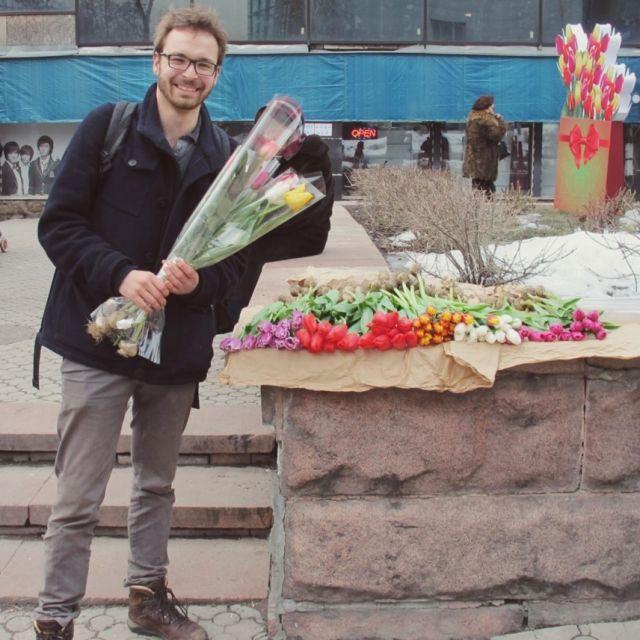 Junger Mann mit Blumensträußen in der Hand posiert vor einem Blumenstand.