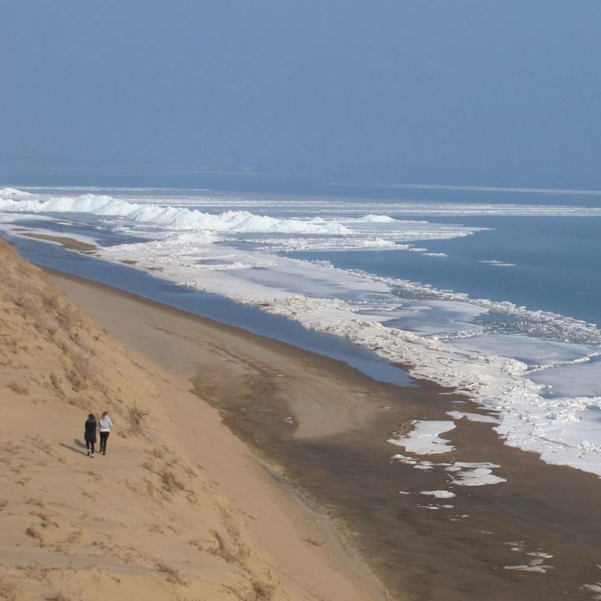 Ufer einer Talsperre mit Sandstrand, im Wasser ist noch Eis und Schnee zu sehen, an Land nicht mehr.