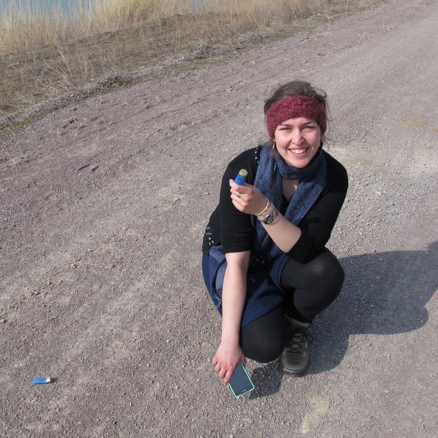 Theresa mit leeren Patronenhülsen in der Hand, die sie auf dem Wanderweg gefunden hat.