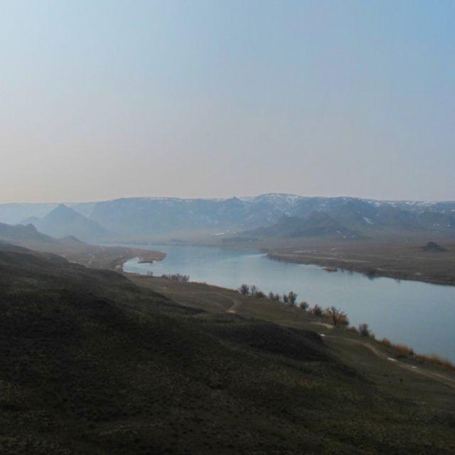Blick von einem Aussichtspunkt auf den Ili-Fluss, umgeben von Bergen