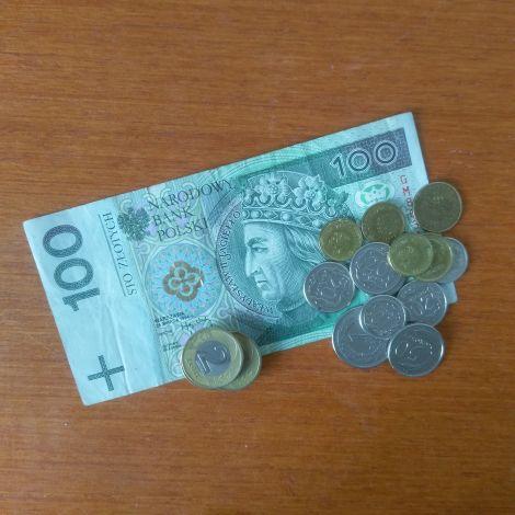 Geldschein (100 Zloty) und daneben einige Münzen (auch Zloty)