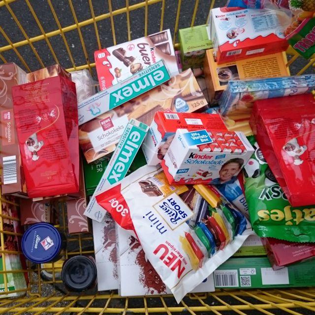 Einkaufswagen gefüllt mit Süßigkeiten, Zahnpasta, Pesto und Kaffeefiltern