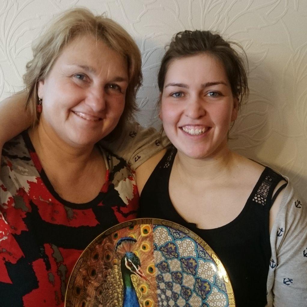 Theresa und ihre Mutter bei der Übergabe des Geburtstagsgeschenks, ein Teller mit kasachischen Ornamenten in Gold, Gelb und Blau