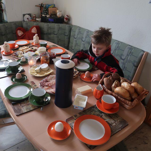 Liebevoll gedeckter Frühstückstisch mit Brötchen, Frühstückseiern, Kaffee und Marmelade