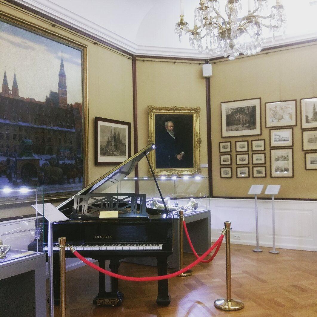 Raum im historischen Museum im Stadtpalast von Wroclaw. Zu sehen ist ein Flügel, an der Wand hängen verschiedene Gemälde.