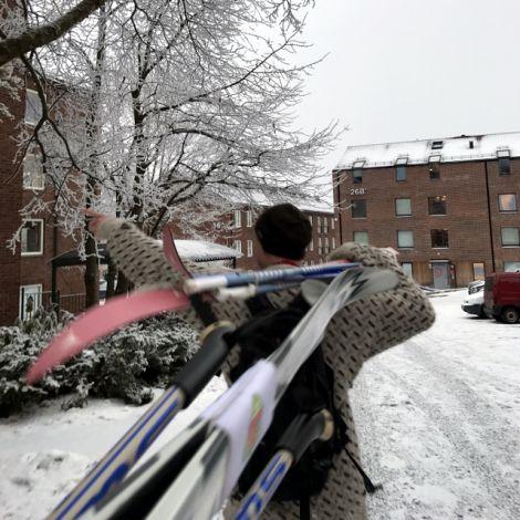 Mann mit Skiern geschultert vor Wohnhäusern