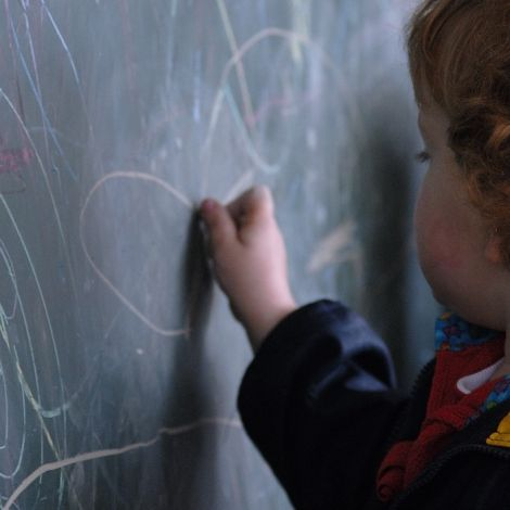 Kind malt an eine Tafel