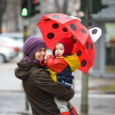 Mutter mit Kind auf dem Arm im Regen mit Regenshirm