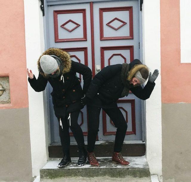 Zwei Mädchen tanzen vor einer Holztür