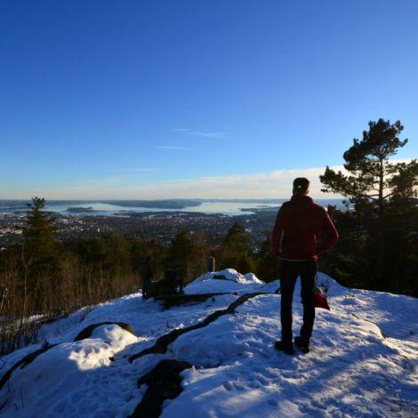 Mann auf verschneitem Gipfel, Blick auf Fjord mit Sonnenuntergang