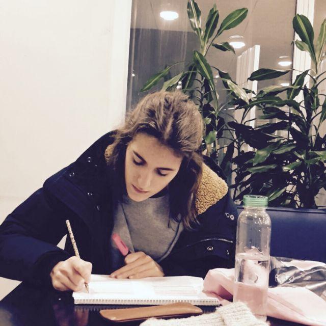 Mädchen vor Schreibtisch mit Lernmaterialien