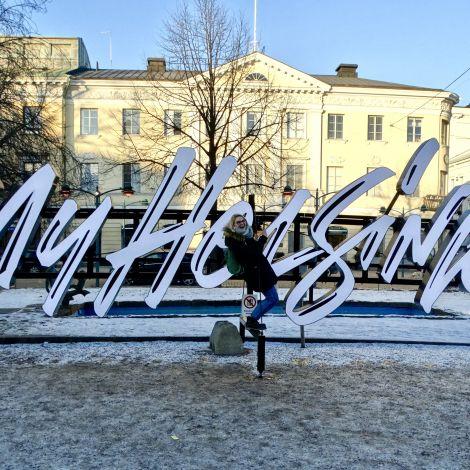 Helsinki Leuchtschriftzug als Reklame mit drei Mädchen die darauf stehen